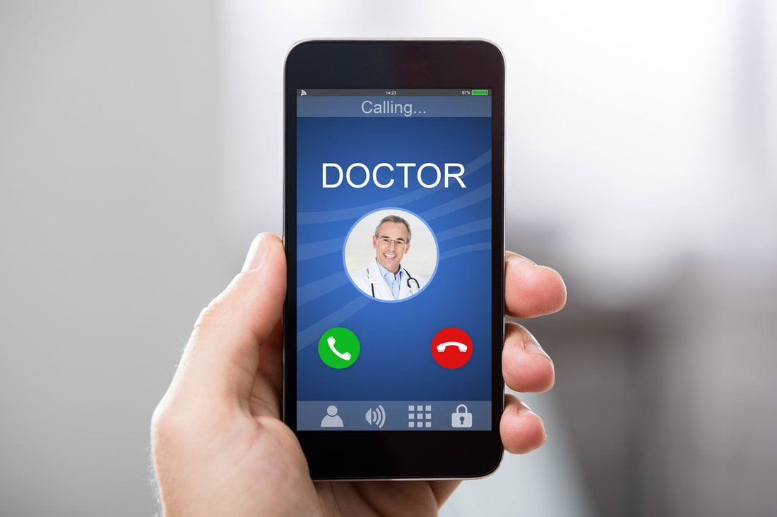 Person holding phone utilizing telemedicine with doctor on the screen.